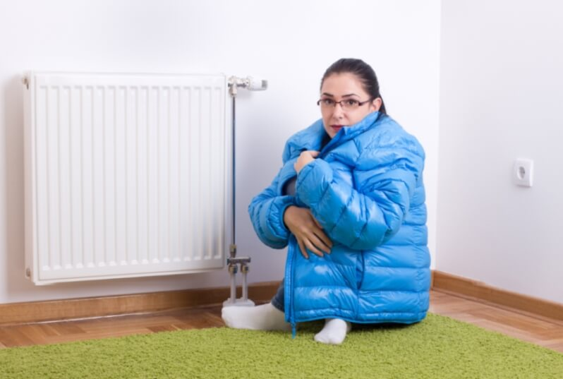 Young woman in blue winter jacket sitting next to cold radiator
