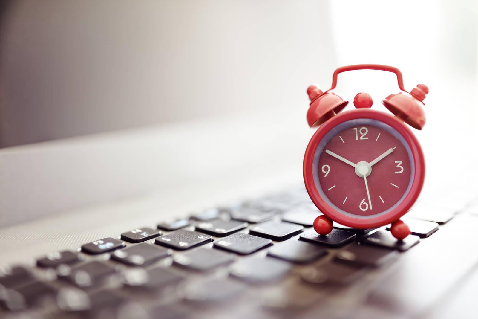 Alarm clock on laptop concept for business deadline