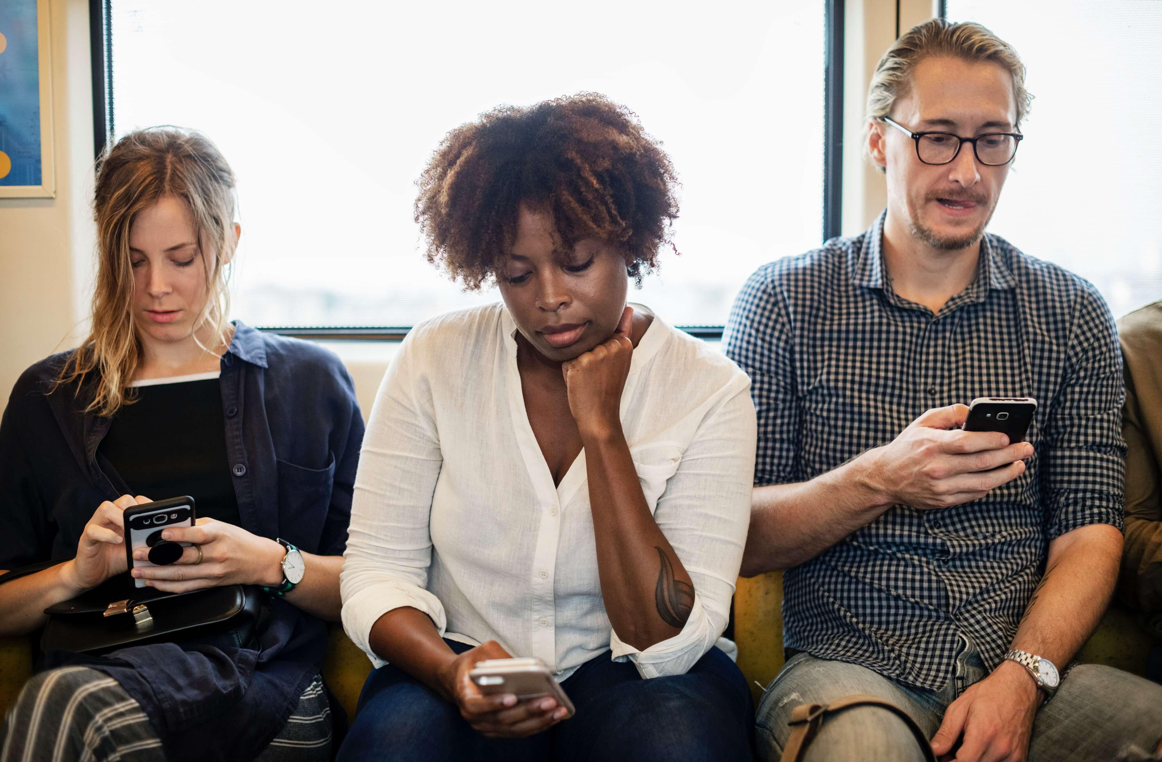Customer Success: duas mulheres e um homem concentrados em seus smartphones