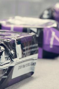 Esteira de produção com produto embalados para correio com a marca da Netshoes