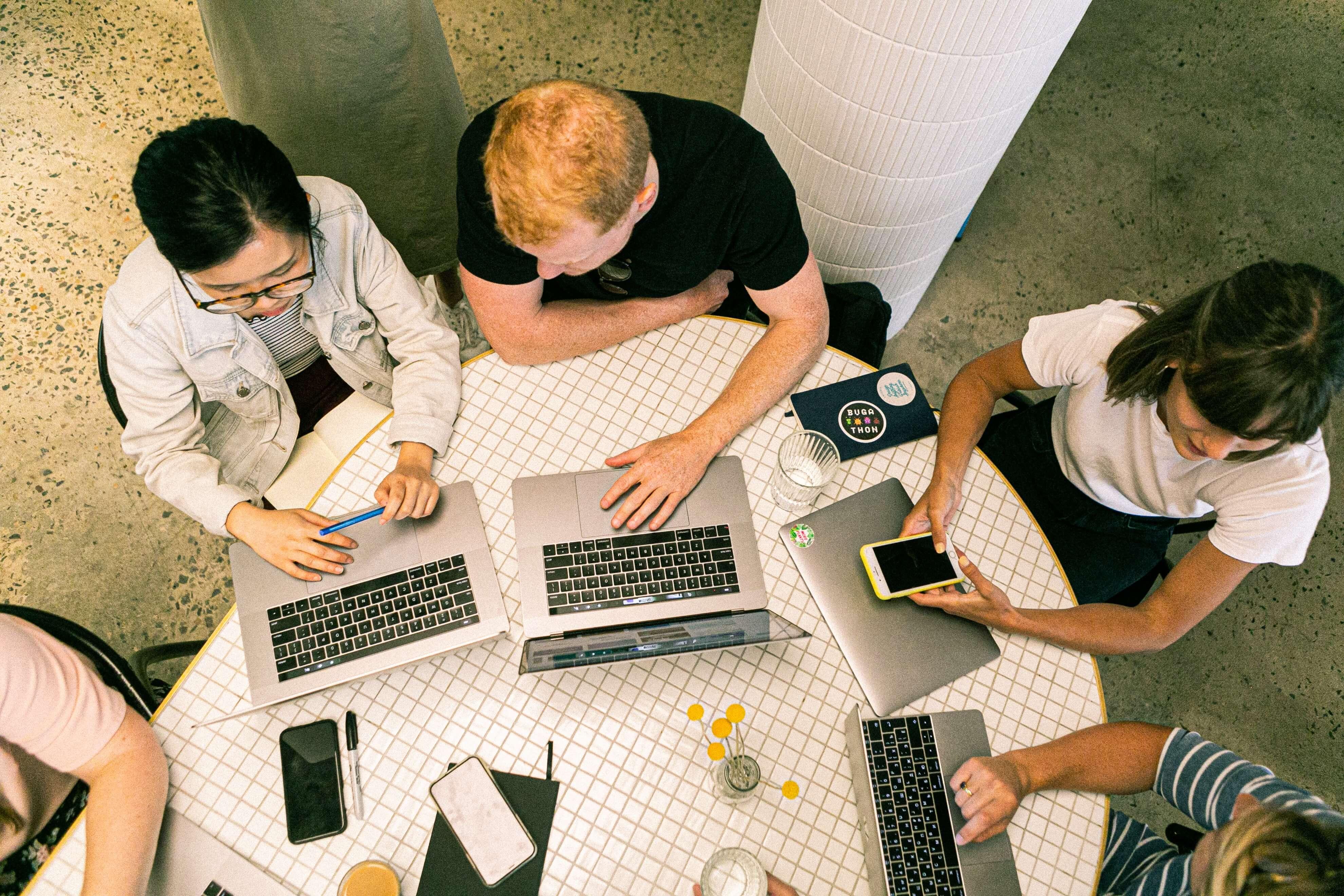 Equipe de cinco pessoas trabalhando com seus notebooks e smartphones